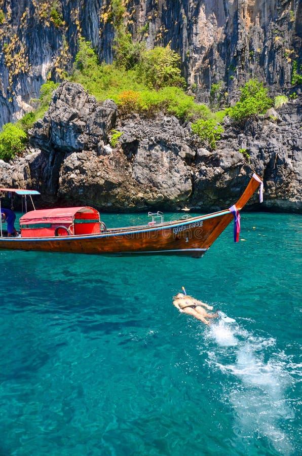 Κολύμβηση με αναπνευστήρα στο υπόβαθρο της ταϊλανδικής βάρκας longtail βαρκών στοκ φωτογραφία