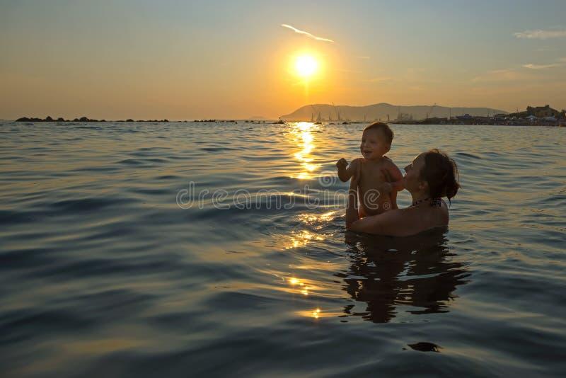 Κολύμβηση στη θάλασσα στο ηλιοβασίλεμα στοκ εικόνες