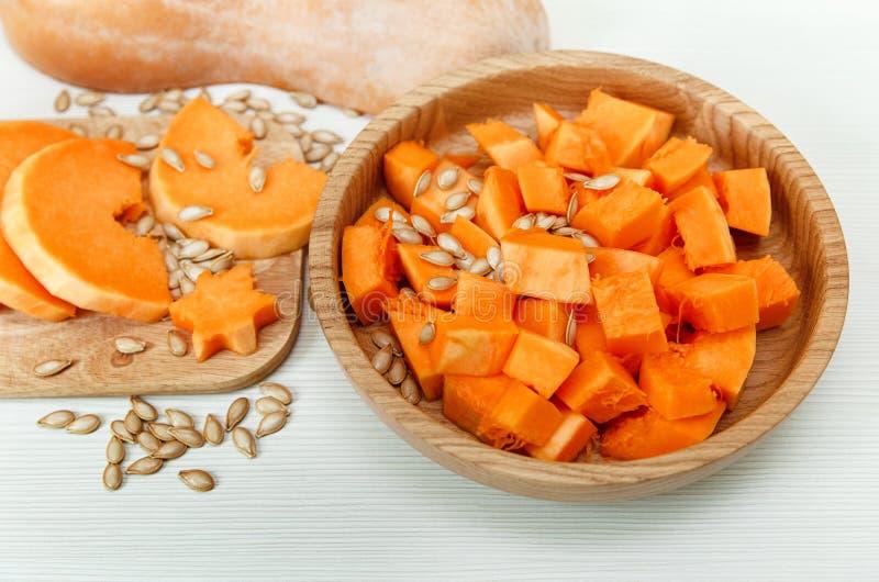 Κομμάτια περικοπών της κολοκύθας με τους σπόρους στο ξύλινο πιάτο στον ξύλινο πίνακα Συγκομιδή, φρέσκο λαχανικό, συστατικό στοκ εικόνες