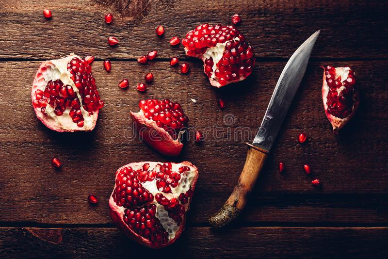 Κομμάτια ροδιών με το μαχαίρι στον ξύλινο πίνακα στοκ φωτογραφίες
