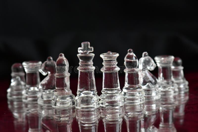 Κομμάτια σκακιού γυαλιού στη σκακιέρα στοκ φωτογραφία