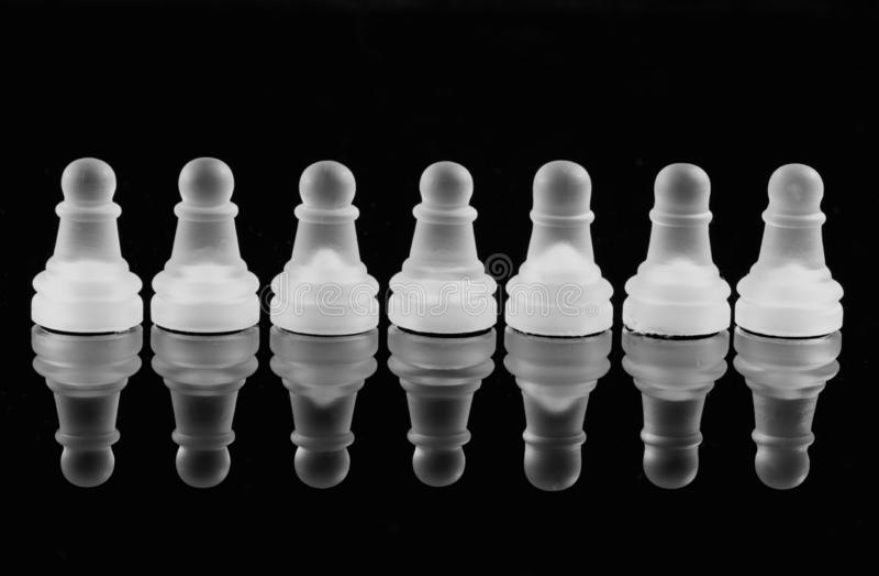 Κομμάτια σκακιού ενέχυρων σε μια μαύρη αντανακλαστική επιφάνεια στοκ εικόνες με δικαίωμα ελεύθερης χρήσης