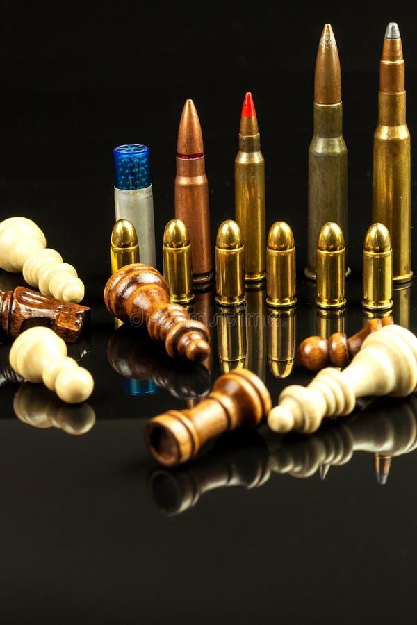Κομμάτια σκακιού και πυρομαχικά σε ένα μαύρο υπόβαθρο Σκάκι παιχνιδιού ματ Η έννοια της ήττας και της νίκης επικίνδυνο παιχνίδι στοκ εικόνες με δικαίωμα ελεύθερης χρήσης
