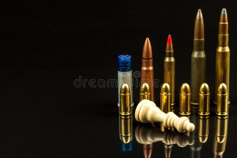 Κομμάτια σκακιού και πυρομαχικά σε ένα μαύρο υπόβαθρο Σκάκι παιχνιδιού ματ Η έννοια της ήττας και της νίκης επικίνδυνο παιχνίδι στοκ φωτογραφία με δικαίωμα ελεύθερης χρήσης