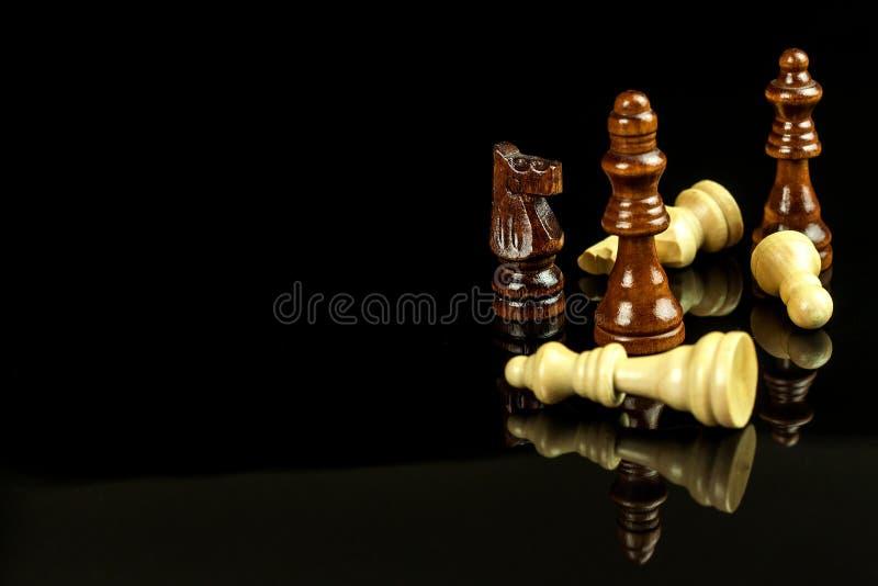 Κομμάτια σκακιού σε ένα μαύρο υπόβαθρο Σκάκι παιχνιδιού ματ Η έννοια της ήττας και της νίκης στοκ εικόνες