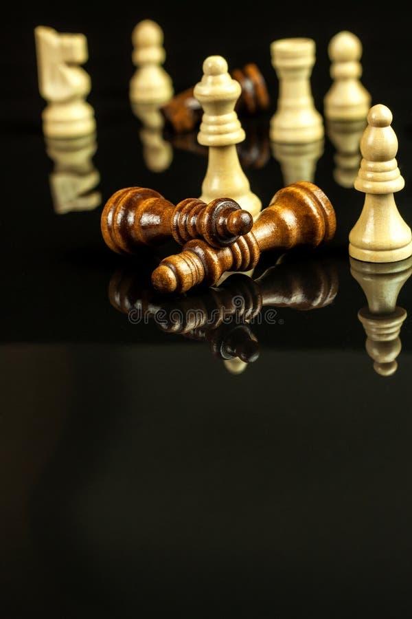 Κομμάτια σκακιού σε ένα μαύρο υπόβαθρο Σκάκι παιχνιδιού ματ Η έννοια της ήττας και της νίκης στοκ φωτογραφίες