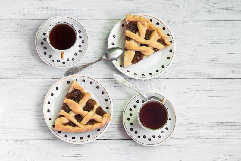 Κομμάτια της ευώδους πίτας κολοκύθας σε έναν ξύλινο πίνακα με τα φλιτζάνια του καφέ στοκ εικόνα