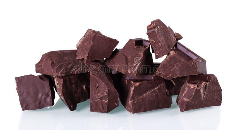 Κομμάτια της πικρής σκοτεινής σοκολάτας που απομονώνονται στο λευκό στοκ φωτογραφίες