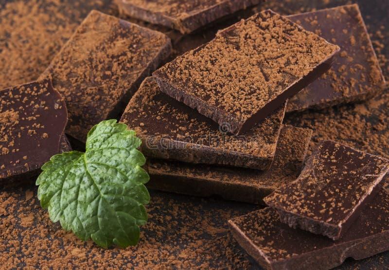 Κομμάτια της σκοτεινής σκόνης σοκολάτας, μεντών και κακάου στοκ φωτογραφία