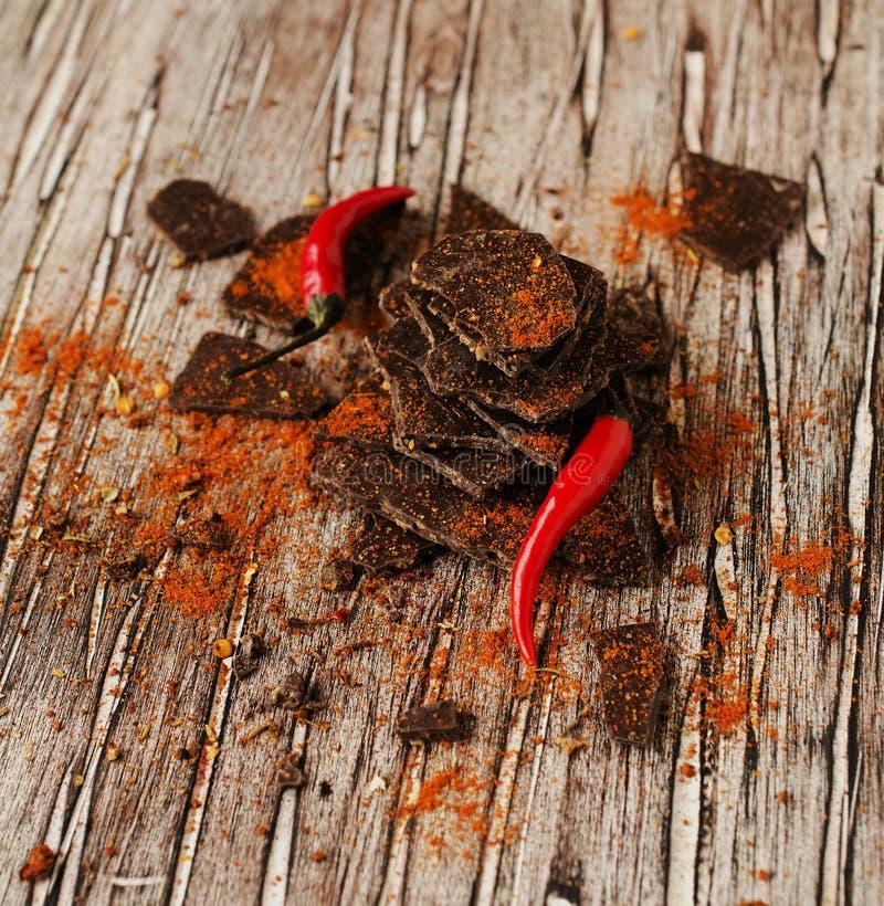 Κομμάτια της σκοτεινής σοκολάτας με τα τσίλι στο μαύρο πίνακα άνθρακα στοκ εικόνες