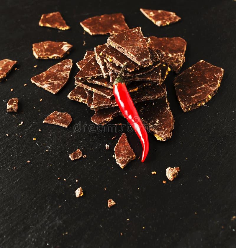 Κομμάτια της σκοτεινής σοκολάτας με τα τσίλι στο μαύρο πίνακα άνθρακα στοκ φωτογραφία με δικαίωμα ελεύθερης χρήσης