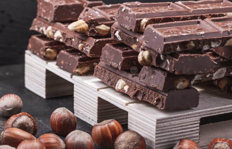 Κομμάτια της σοκολάτας με ολόκληρα τα φουντούκια Στην παλέτα Καφετιά τονικότητα στοκ εικόνες
