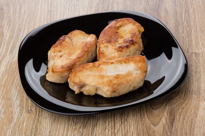 Κομμάτια του τηγανισμένου κρέατος της Τουρκίας στο μαύρο πιάτο στον πίνακα στοκ εικόνα