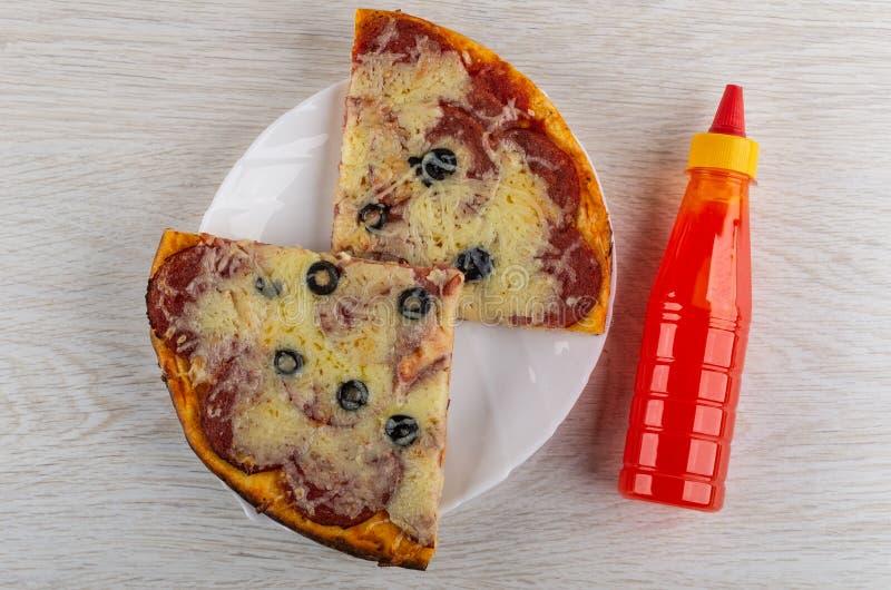 Κομμάτια pepperoni πιτσών στο πιάτο, μπουκάλι του κέτσαπ στον πίνακα r στοκ φωτογραφίες με δικαίωμα ελεύθερης χρήσης