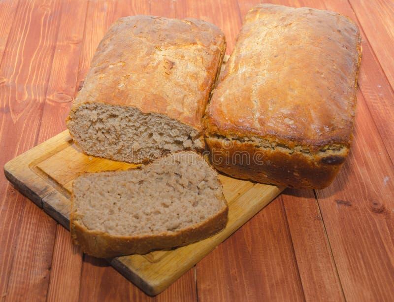 Κομμάτι και δύο φραντζόλες του φρέσκου ψωμιού σε έναν ξύλινο πίνακα στοκ εικόνες