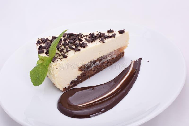 Κομμάτι ορεκτικό cheesecake με τα τσιπ σοκολάτας σε ένα άσπρο πιάτο στοκ εικόνες