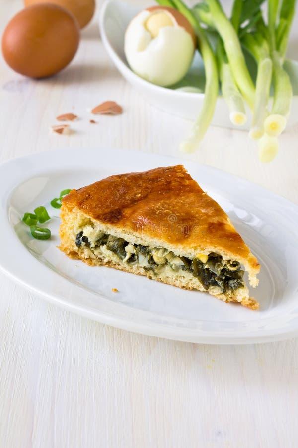 Κομμάτι της πίτας με τα τεμαχισμένα πράσινα κρεμμύδια άνοιξη στοκ εικόνες