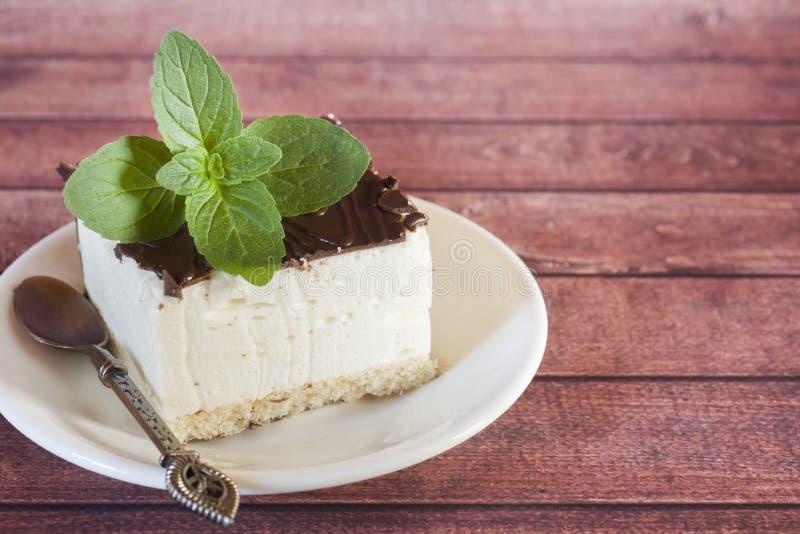 Κομμάτι του εύγευστου souffle κέικ στη σοκολάτα σε ένα σκοτεινό υπόβαθρο με ένα κλαδάκι της μέντας στοκ εικόνες