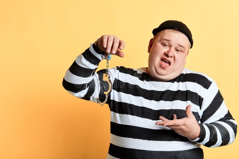 Κομμάτι του κέικ, παχύς παχουλός εγκληματίας που παρουσιάζει σπασμένη χειροπέδη στοκ εικόνες