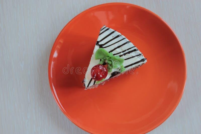 Κομμάτι του κέικ σε ένα πορτοκαλί πιάτο στοκ εικόνα