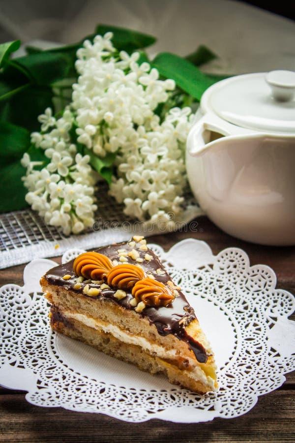 Κομμάτι του κέικ, teapot και της πασχαλιάς σε ένα ξύλινο υπόβαθρο στοκ εικόνα με δικαίωμα ελεύθερης χρήσης