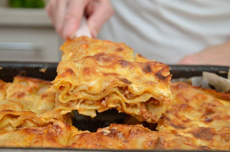 Κομμάτι του καυτού juicy lasagna στο δίσκο ψησίματος στοκ εικόνες