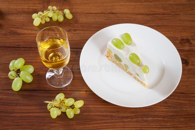 Κομμάτι του σταφυλιού torte με τα πράσινα σταφύλια στο πιάτο, άσπρα glas κρασιού στοκ φωτογραφία με δικαίωμα ελεύθερης χρήσης