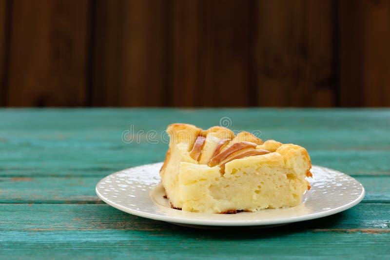Κομμάτι του syrnik, ελαφριά πίτα θεωρητικών και υποατομικών σωματιδίων με τα μήλα στον παλαιό ξύλινο πίνακα στοκ εικόνες με δικαίωμα ελεύθερης χρήσης
