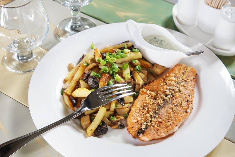 Κομμάτι των τηγανισμένων ψαριών με τις πατάτες σε έναν τοποθετημένο πίνακα στοκ εικόνες