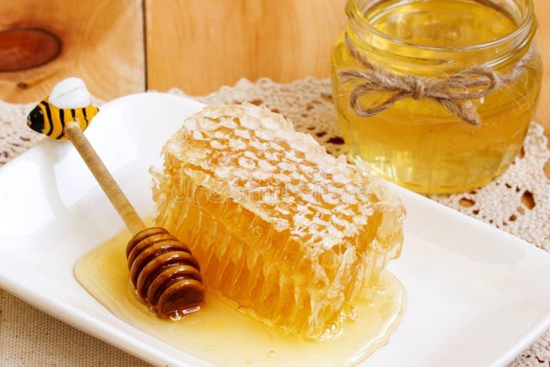 Κομμάτι χτενών μελιού Φέτα μελιού με το κουτάλι μελιού και το βάζο του μελιού στον ξύλινο πίνακα κυψελωτό μέρος με το κερί και το στοκ εικόνα