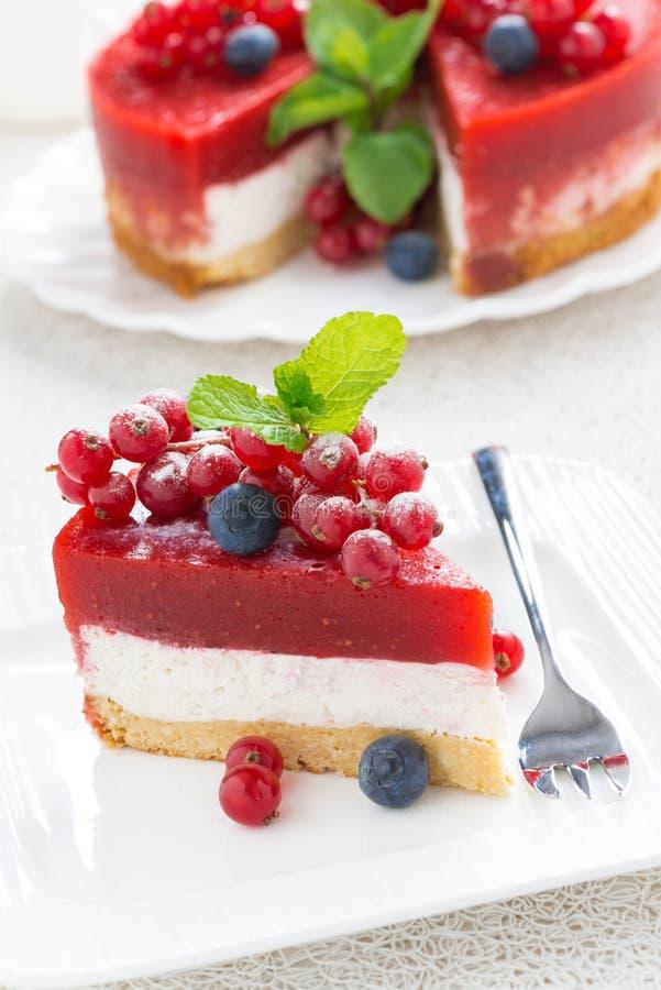 Κομμάτι cheesecake με τη ζελατίνα μούρων σε ένα άσπρο πιάτο στοκ φωτογραφία