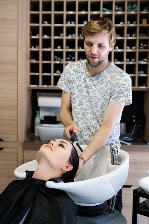 Κομμωτής ατόμων που πλένει τον επικεφαλής πελάτη Ένας κύριος τρίχας ατόμων που ποτίζει μια τρίχα κοριτσιών ` s με ένα ντους σε έν στοκ εικόνες