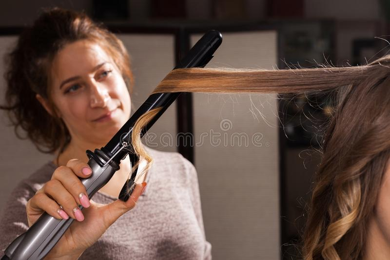 Κομμωτής που κάνει ένα hairdo με τις μπούκλες σε ένα πρότυπο στοκ εικόνες