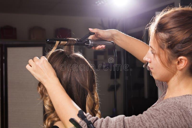Κομμωτής που κάνει μια τρίχα κατσαρώνοντας σε μια γυναίκα στοκ φωτογραφίες