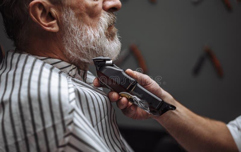 Κομμωτής που κάνει τον προσδιορισμό με την ηλεκτρική ξυριστική μηχανή για τον ηληκιωμένο στο κατάστημα κουρέων στοκ εικόνα