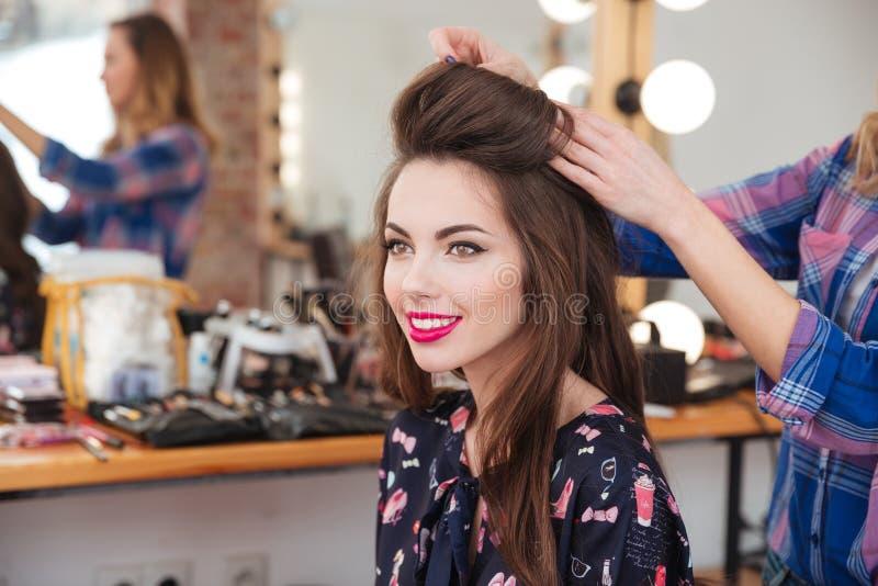 Κομμωτής που κάνει hairstyle στην εύθυμη γυναίκα με μακρυμάλλη στοκ εικόνα
