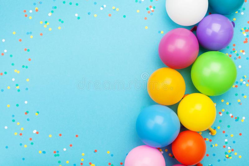 Κομφετί και ζωηρόχρωμα μπαλόνια για τη γιορτή γενεθλίων στην μπλε άποψη επιτραπέζιων κορυφών επίπεδος βάλτε το ύφος στοκ εικόνα με δικαίωμα ελεύθερης χρήσης