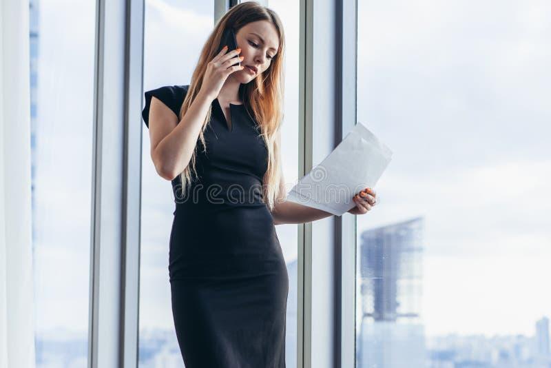 Κομψά νέα θηλυκά έγγραφα εκμετάλλευσης ιδιοκτητών επιχείρησης που μιλούν στο κινητό τηλέφωνο που συζητά τους όρους συμβάσεων που  στοκ φωτογραφία