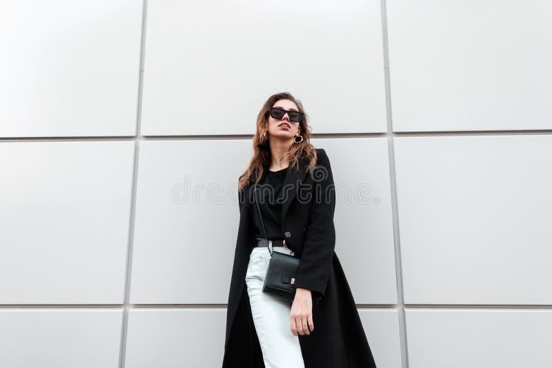 Κομψή αρκετά νέα γυναίκα hipster στα σκοτεινά καθιερώνοντα τη μόδα γυαλιά ηλίου σε ένα μοντέρνο μακρύ παλτό στα εκλεκτής ποιότητα στοκ εικόνες με δικαίωμα ελεύθερης χρήσης