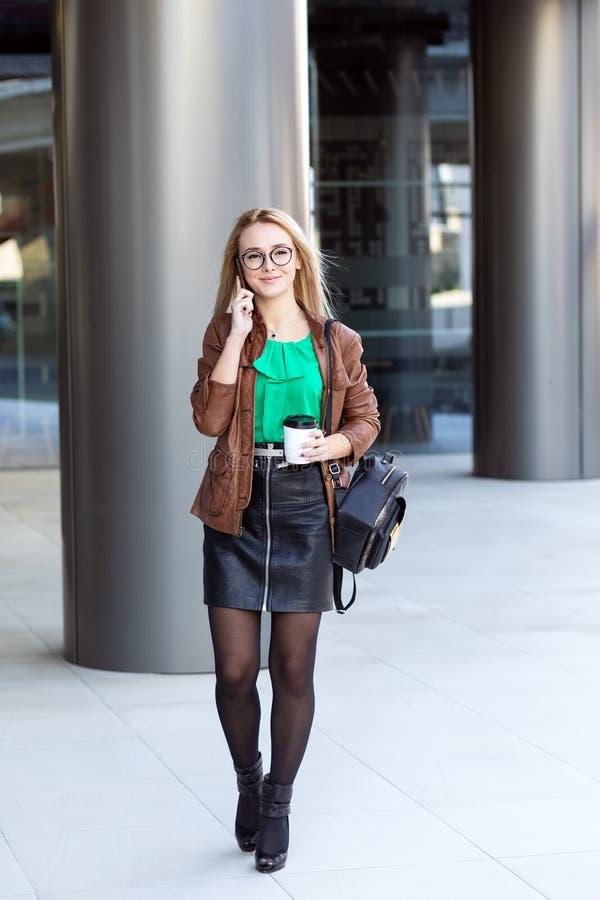 Κομψή γυναίκα με τα μοντέρνα γυαλιά που πίνουν τον καφέ και που έχουν μια τηλεφωνική συνομιλία έξω από το σύγχρονο κτίριο γραφείω στοκ φωτογραφία