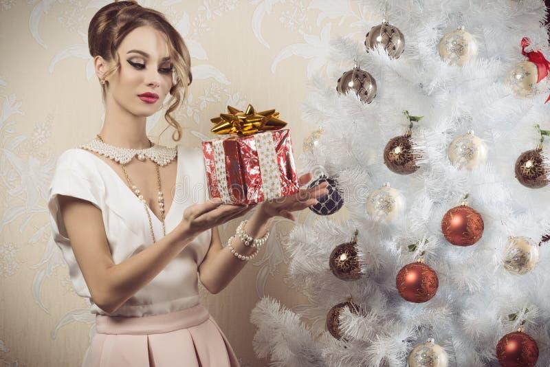 Κομψή γυναίκα με το δώρο Χριστουγέννων στοκ φωτογραφίες