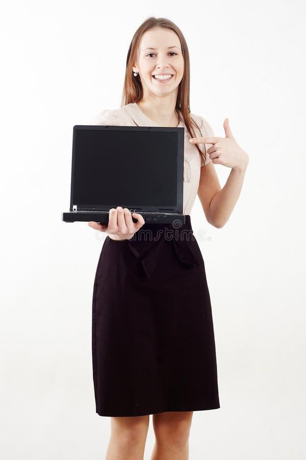 Κομψή γυναίκα που εμφανίζει ένα lap-top και χαμόγελο στοκ εικόνα με δικαίωμα ελεύθερης χρήσης