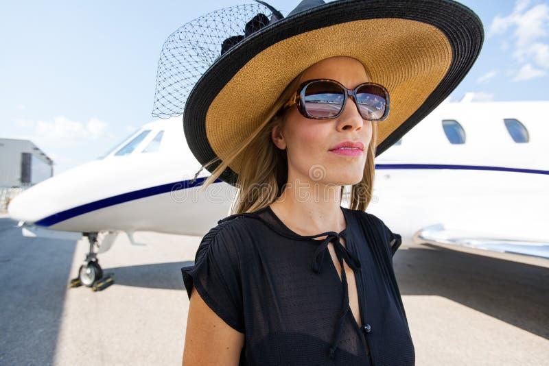 Κομψή γυναίκα που στέκεται ενάντια στο ιδιωτικό αεριωθούμενο αεροπλάνο στοκ εικόνα με δικαίωμα ελεύθερης χρήσης