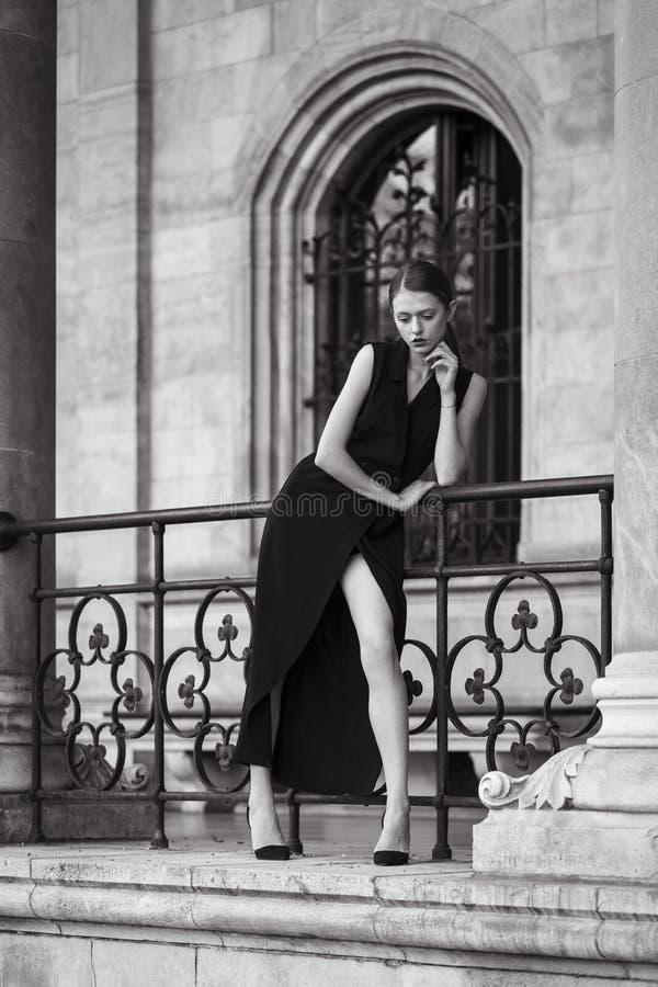 Κομψή γυναίκα που στέκεται στις αψίδες της κλασσικής αρχιτεκτονικής στοκ εικόνες