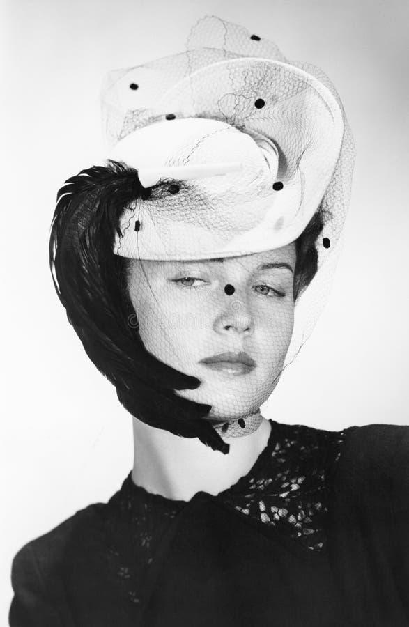 Κομψή γυναίκα που φορά ένα ενδιαφέρον καπέλο με ένα πέπλο (όλα τα πρόσωπα που απεικονίζονται δεν ζουν περισσότερο και κανένα κτήμ στοκ φωτογραφία με δικαίωμα ελεύθερης χρήσης