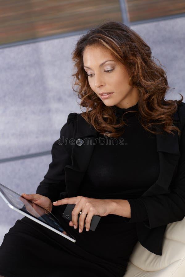 Κομψή γυναίκα που χρησιμοποιεί τον υπολογιστή ταμπλετών στοκ εικόνες