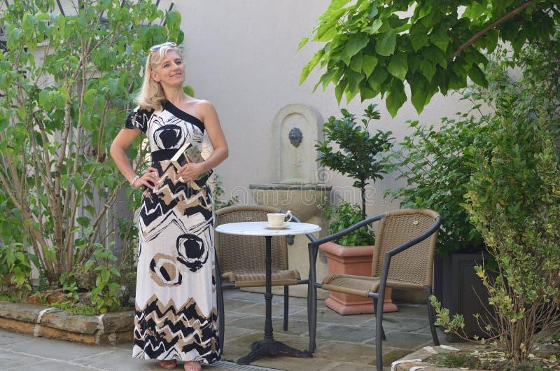Κομψή γυναίκα σε έναν θερινό κήπο στοκ εικόνες