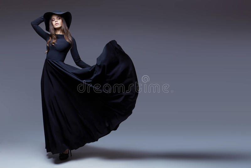 Κομψή γυναίκα σε ένα καπέλο και κυματίζοντας ένα πολύ φόρεμα στοκ εικόνα