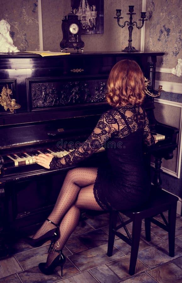 Κομψή γυναίκα στο μαύρο φόρεμα που παίζει το πιάνο Όμορφα θηλυκά πόδια στις γυναικείες κάλτσες και τα τακούνια στοκ εικόνα με δικαίωμα ελεύθερης χρήσης
