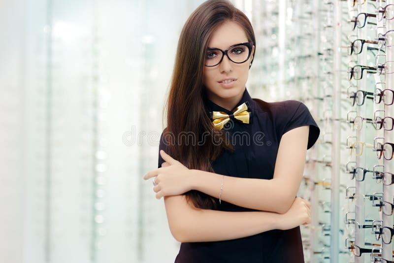 Κομψή γυναίκα Bowtie με τα γυαλιά πλαισίων ματιών γατών στο οπτικό κατάστημα στοκ εικόνες